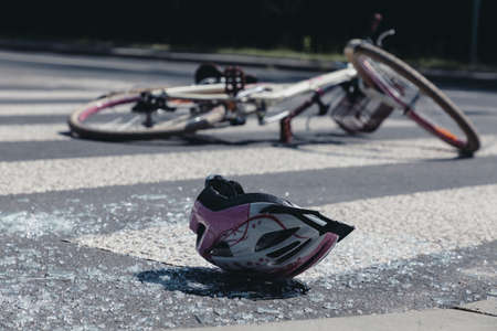 White and pink teenage girls helmet lying on broken glass after terrible car crash