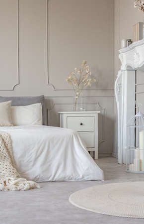 White wooden fireplace portal in beautiful bedroom interior with white sheets on king size bed Stockfoto