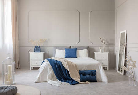 Blue pillow and blanket on white bed in spacious bedroom interior, copy space on empty grey wall Stockfoto