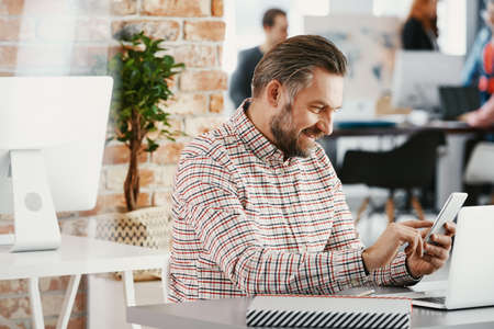 Smiling entrepreneur using smartphone while working in the office of international company