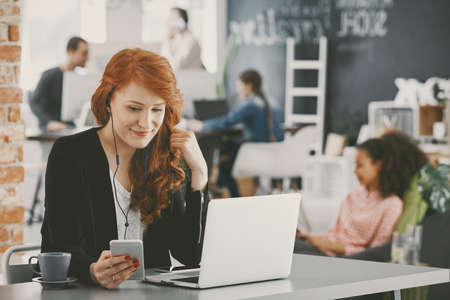 Smiling businesswoman using laptop and smartphone while working in a finance agency
