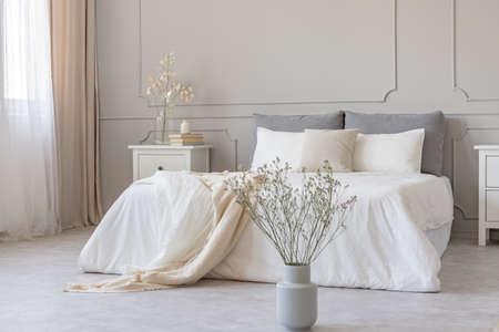 White flowers in vase in elegant grey bedroom interior with simple bedding
