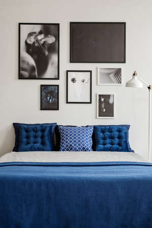 Navy blue bedding on king size bed in stylish interior with galley of framed artwork on the wall. Real photo concept Stockfoto