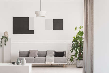Flowers in vase on coffee table in front of grey Scandinavian couch with pillows