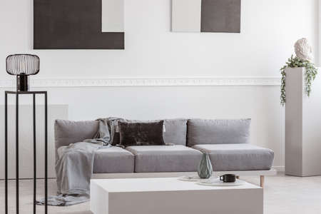 Grey blanket and black pillow on comfortable sofa in stylish living room interior