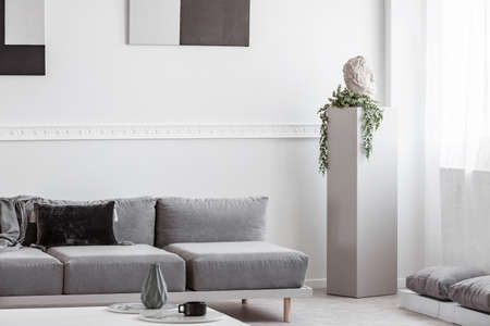 Grey concrete column with head and green flower in monochromatic living room interior