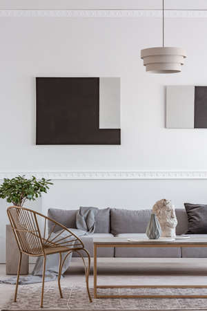 Stylish golden chair next to coffee table with vase in front of grey couch