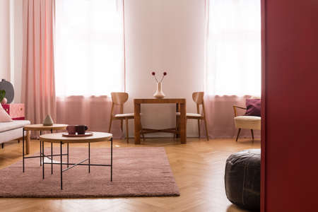 Wooden tables on purple carpet in living room interior with pink drapes at window. Real photo