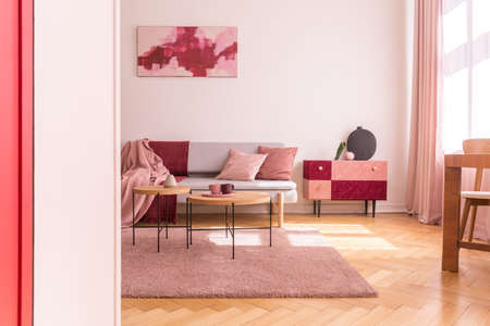 Poster above couch with pink pillows in loft interior with wooden tables on purple carpet. Real photo