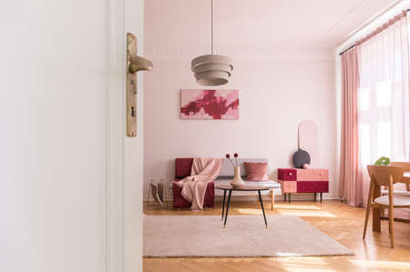 White door of living room with poster above couch near table with flowers on pink carpet. Real photo