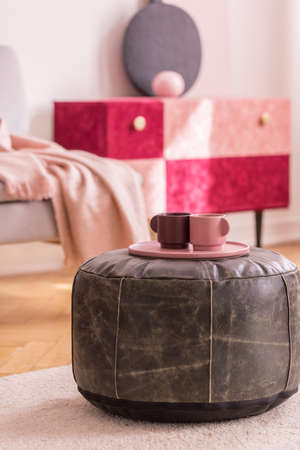 Pink plate with cups on leather pouf on pastel carpet in living room interior with cabinet. Real photo