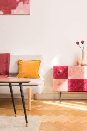 Gelbes Kissen auf Sofa neben rotem und rosafarbenem Schrank mit Blumen im flachen Innenraum mit Tisch. Echtes Foto