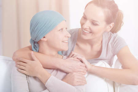 Smiling woman hugging happy sick person with cancer wearing headscarf