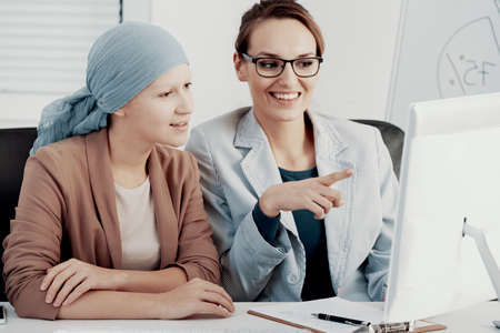 Smiling businesswoman working with colleague with cancer during meeting in the office