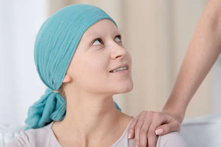 Happy woman with leukemia wearing headscarf while friendly person supporting her