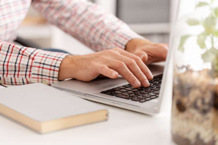 Closeup of freelance journalist typing on laptop keyboard at home office Stockfoto