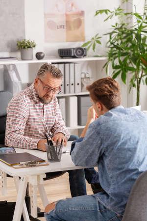 Vorstellungsgespräch mit einem gutaussehenden Senior-Chef und einem rebellischen Teenager-Mann im Büro der Casual Corporation Standard-Bild