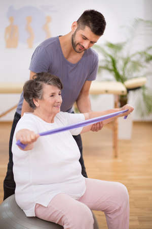 Elderly woman exercising with stretching tapes with her physiotherapist