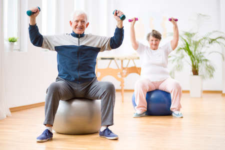 Two elderly people holding weights and sitting on exercising balls
