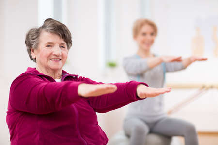 Smiling elderly lady holding her arms during pilates for seniors