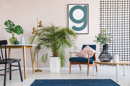 Big palm plant in white pot in stylish living and dining room interior with round table and vintage armchair with pastel pink pillow