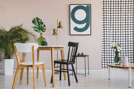 Modern poster on pastel pink wall of elegant living room interior with round wooden table with chairs