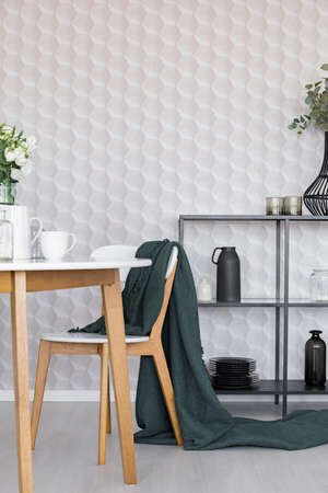 Dark green blanket on wooden chair next to table in stylish dining room interior with metal shelf with plates and jugs and geometric pattern on wallpaper