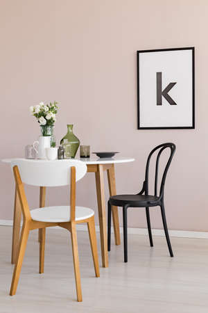White jug, coffee cup and flowers in glass vase on white wooden dining table in spacious living room interior with poster on pastel pink wall
