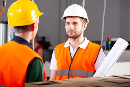 Young handsome plant worker in orange safety jacket and white helmet Stockfoto