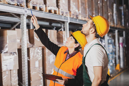 Two warehouse workers in green uniforms and yellow safety helmets Stockfoto