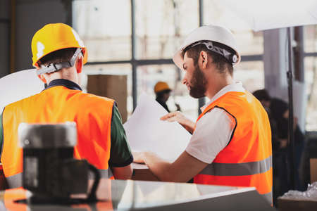 Two factory workers in orange safety jackets and helmets studying delivery documents Stockfoto