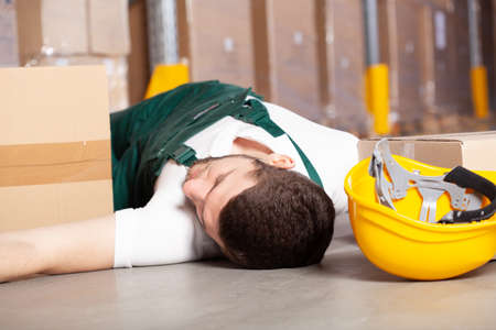 wounded worker lying on the floor after Dangerous accident in warehouse during work