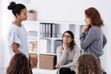 Two brave women standing and looking at each other during role paying at psychotherapy support meeting Stockfoto
