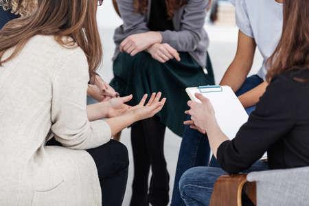 Anonieme vrouwen zitten in kring tijdens groepsbijeenkomst Stockfoto