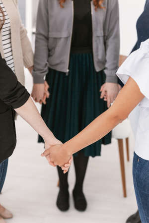 Closeup of group of females standing in circle holding hands during support group meeting 스톡 콘텐츠 - 123114763