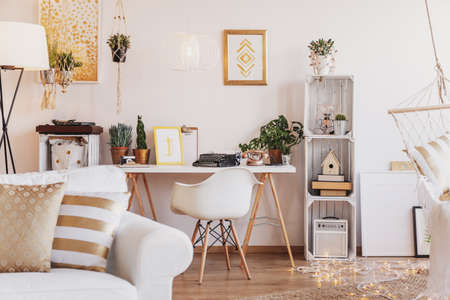 Sofa with cushions in blurred foreground in real photo of bright room interior with fresh plants, gold posters, lights on the floor and desk with typewriter Stockfoto