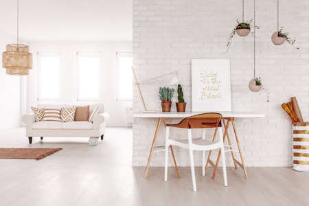 Open space white flat interior in real photo with desk with poster, lamp and fresh plants on brick wall and couch with pillows in the background Stockfoto