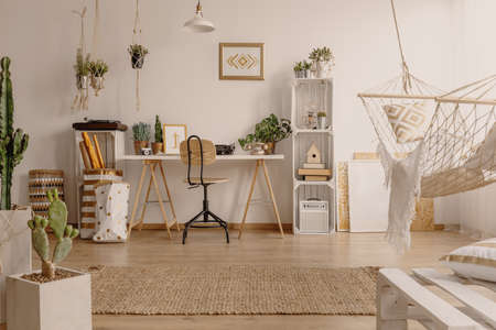 White home office room interior with fresh plants, rug on the floor, hammock with pillow and desk for work in the real photo Stockfoto