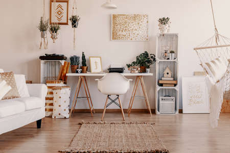 Echtes Foto von hellem Wohnzimmer mit Teppich auf dem Boden, Remote-Arbeitstisch mit Schreibmaschine, frischen Pflanzen und Oldschool-Telefon und goldenen Postern an der Wand
