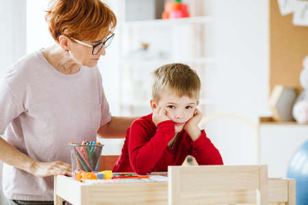 Cute little boy with problems during meeting with therapist