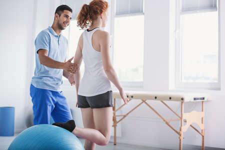 Fysiotherapeut die vrouw ondersteunt tijdens revalidatie met bal
