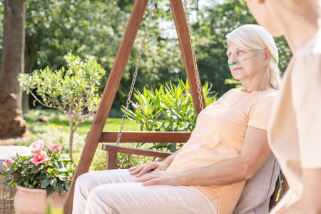 Worried daughter and ill mother spending time together in the garden of hospice