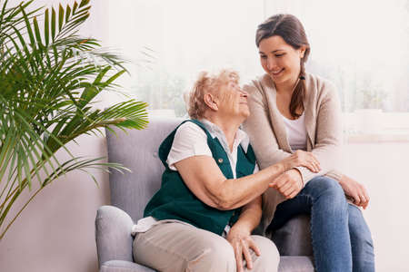 Senior lady sitting in armchair at nursing home, supporting nurse behind her