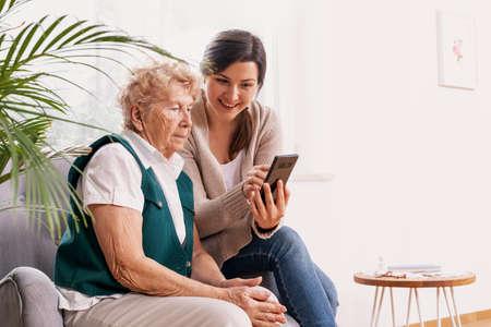 Ältere Frau im Pflegeheim mit ihrer Enkelin, die ihr zeigt, wie man ein Mobiltelefon benutzt