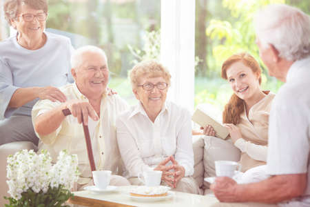 Smiling senior people and happy caregiver drinking tea in the nursing house