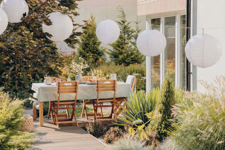 Lanterns and plants on the terrace of house with wooden chairs at table with food and drink. Real photo