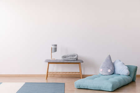 Pillows on blue mattress next to bench with lamp in white simple kid's bedroom interior. Real photo