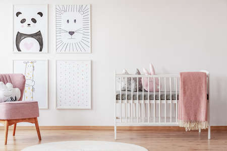 Różowe krzesło w pobliżu kołyski z kocem w białym pokoju dziecka z plakatami i dywanikiem. Prawdziwe zdjęcie