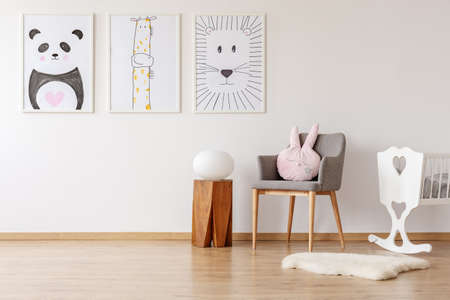 Pink cushion on grey chair next to cradle in white baby's room interior with posters. Real photo Foto de archivo