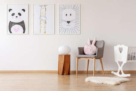 Rosa Kissen auf grauem Stuhl neben der Wiege im Innenraum des weißen Babys mit Postern. Echtes Foto